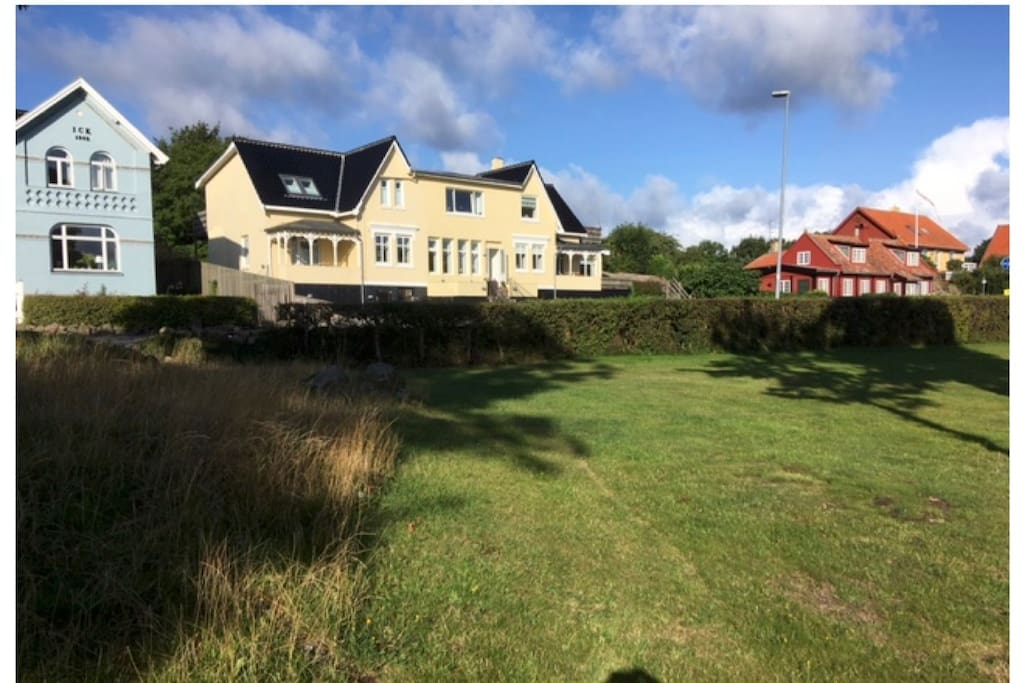 Huset set fra det grønne område, som ligger mellem huset og havet. Lejligheden er den midterste i stueetagen.