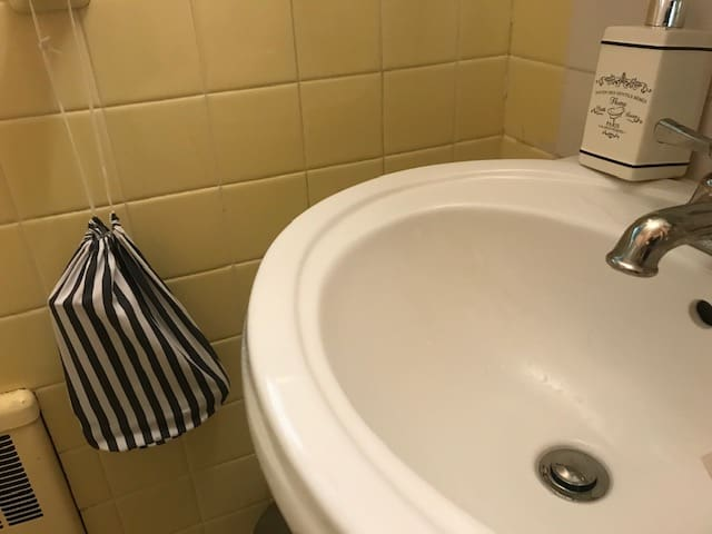 A stripy bag with a hairdryer is easy to spot in a bathroom near a sink.