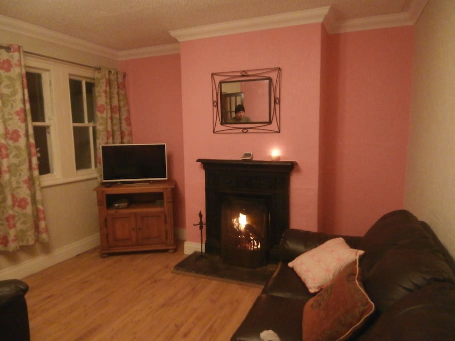 Cosy TV room/dining area, with comfortable seating, open fire and kitchen table