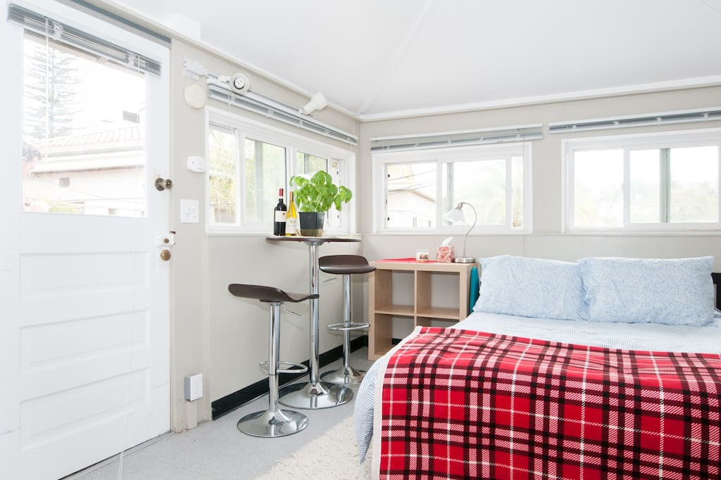 Queen size bed, tall table with two adjustable stools. Tons of light through many double-paned windows. Note: window on door is not double-paned.