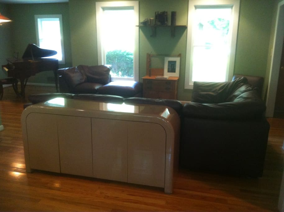 Open living room includes baby grand piano
