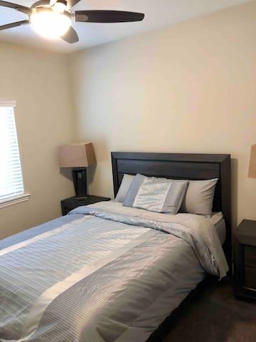 Queen bedroom #2 with ceiling fan, nightstands with lamps. Closet with hangers. Mirror