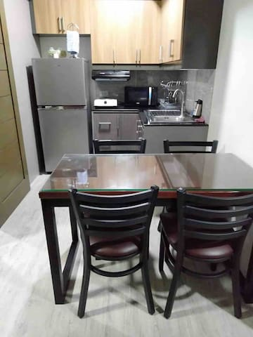 Full service kitchen with lots of storage space. Rice cooker and electric kettle are stowed inside the lower cabinets. Dining table sits 4