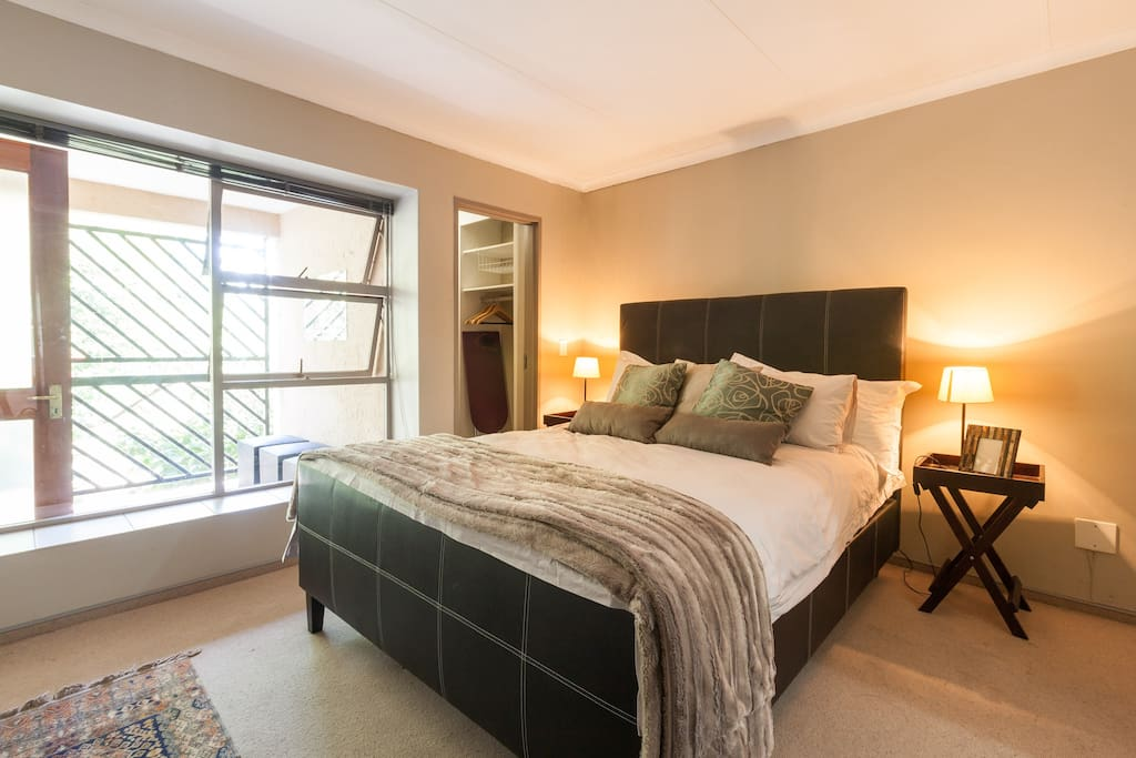 Main bedroom with an extra length queen sized bed extra length pillows all covered in the highest quality cotton linen. The main bedroom boasts a small en suite bathroom with a shower as well as a large walk in wardrobe with a set of wooden hangers.