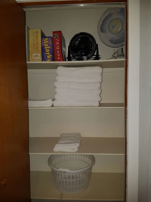 Towels, laundry basket, extra fans and games in the linen closet.