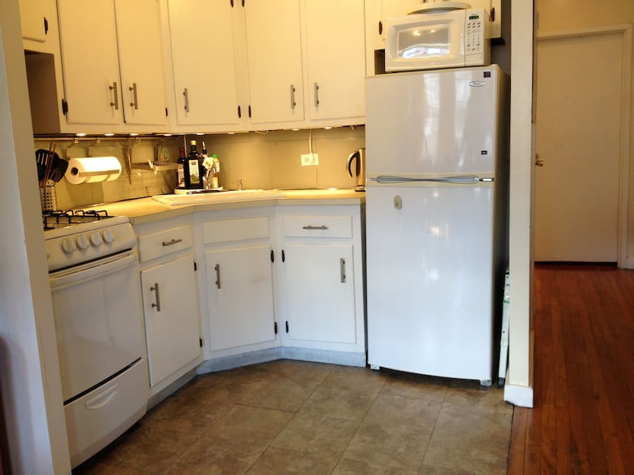 Fully equipped kitchen with gas stove, oven, microwave, electric kettle, slow cooker and other appliances