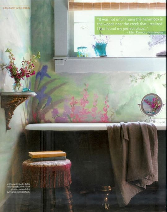 One of two indoor bathrooms has old fashioned clawfoot tub. Walls painted by local artist.