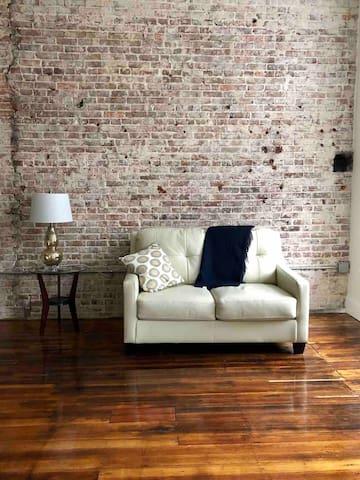 Loveseat and historic brick walls