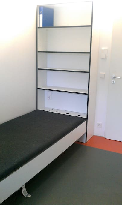 This is the main bed of the room with the shelves in the back
