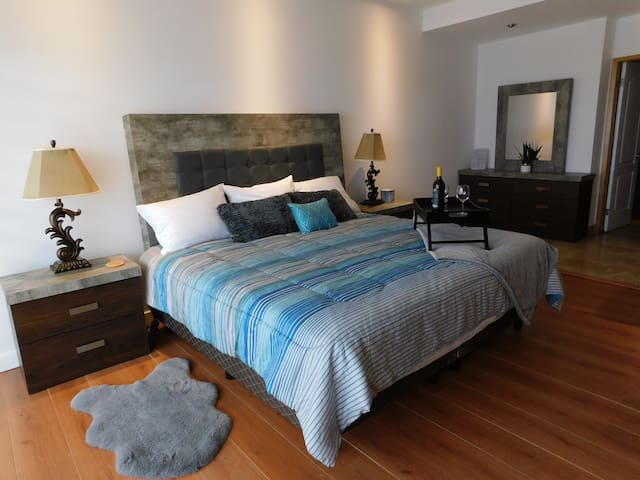 Main bedroom is a foam king bed with a beautiful headboard, two nightstands and a dresser with a mirror.