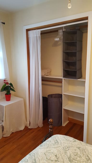 Laptop stand and spacious closet with hangers and organizer. Extra blankets, comforter, and laundry hamper.