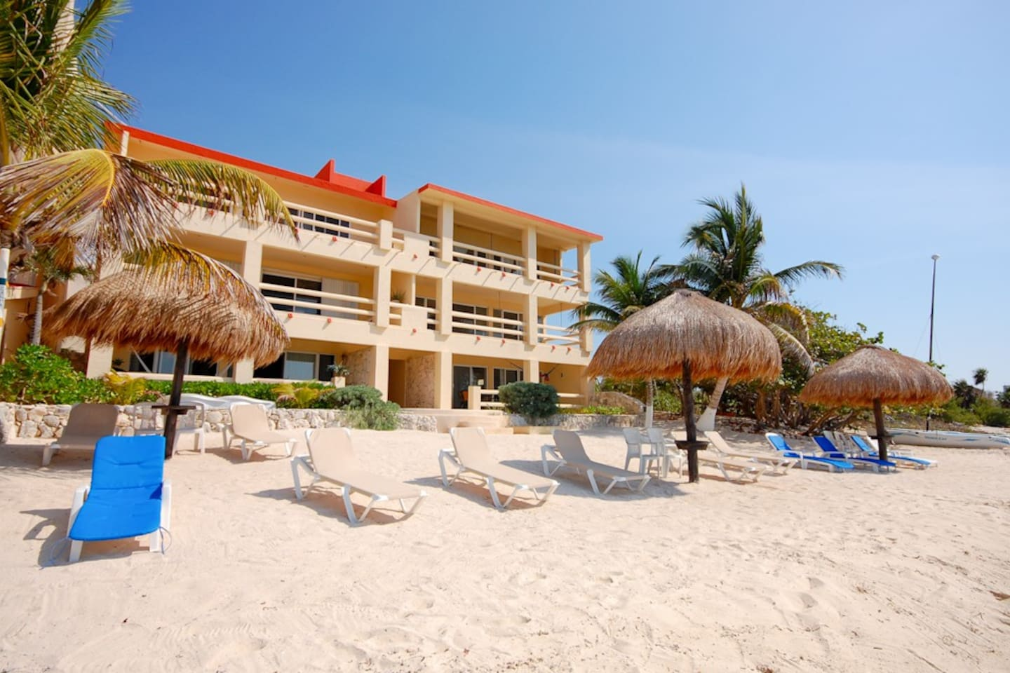 La Mirage Condominiums at Half Moon Bay beach in Akumal.  Loungers and shade palapas are for guest use.