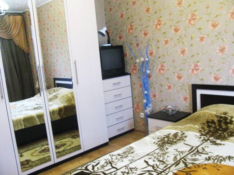 Шкаф с большим зеркалом, пастельное белье, полотенца.