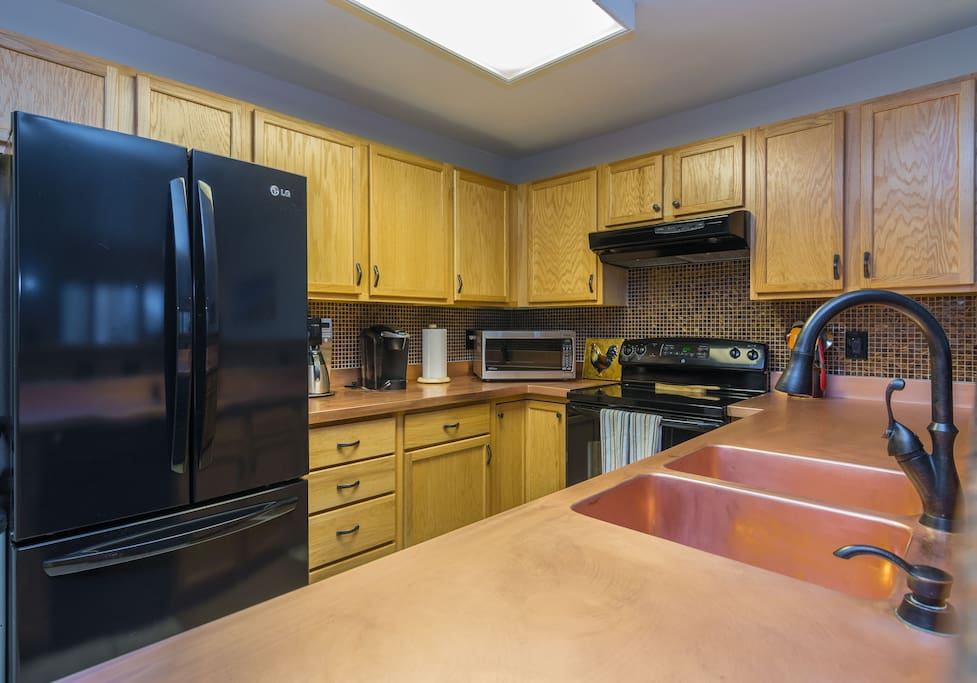 A spacious kitchen has a statement copper countertop and stainless steel appliances
