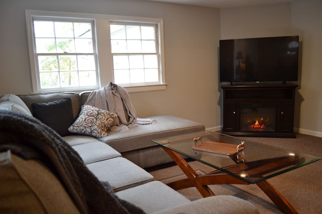 """Living room features a sectional sofa, a futon, electric fireplace and 55"""" flat screen"""