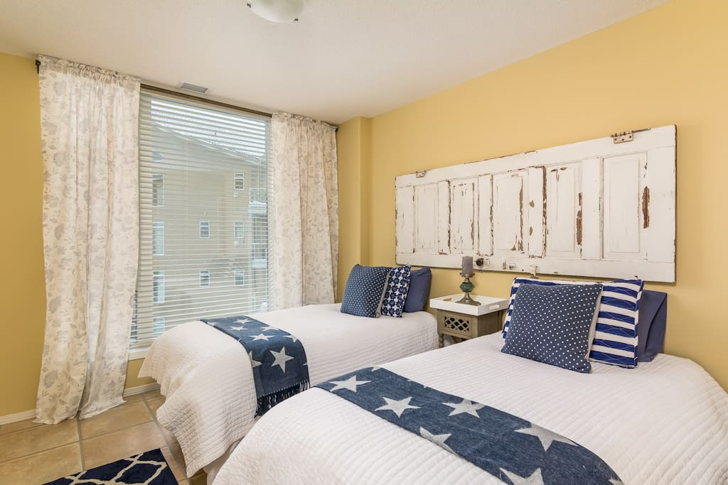 Bedroom 2 with two twin beds and large window facing the lagoon and views of Okanagan Lake.