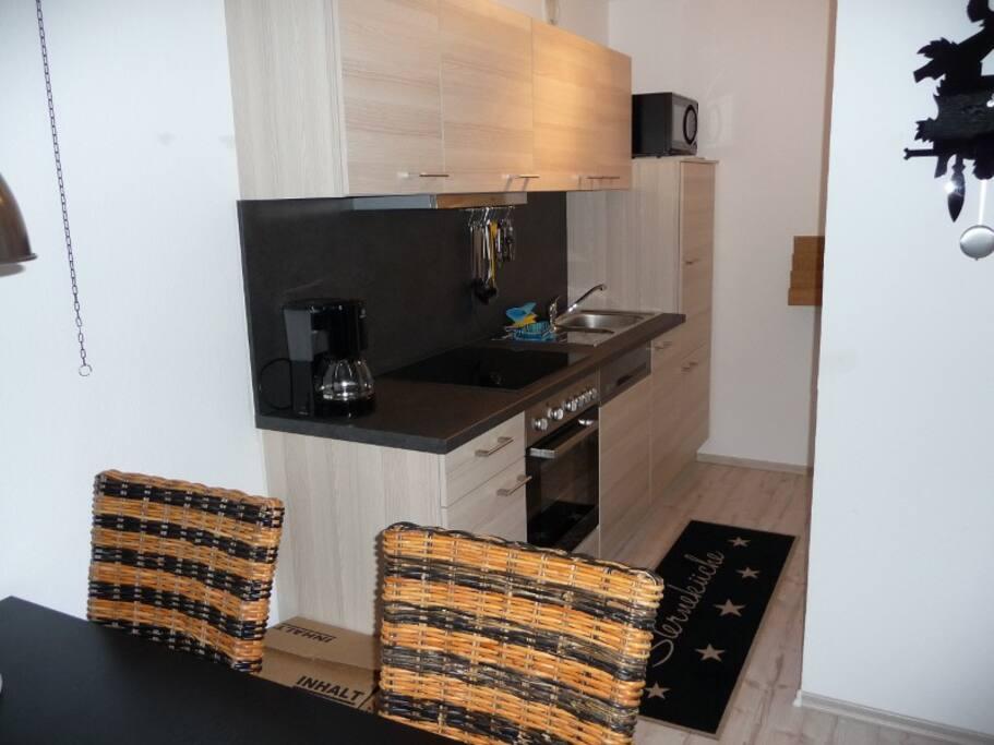 Küche mit Mikrowelle, Backofen, Geschirrspülmaschine, Kaffeemaschine,  Toster und allen Kochutensilien