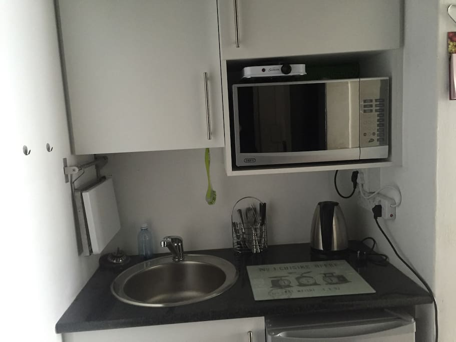 Kitchenette with microwave, fridge, kettle, toaster and one plate stove. Includes crockery and cutlery.