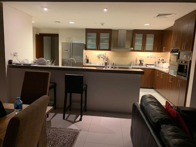 The shared open-plan kitchen with a built-in coffee machine, combination microwave, stove and oven. There is a dishwasher and a large shared refrigerator. (There is an additional refrigerator upstairs in one of the storage areas).