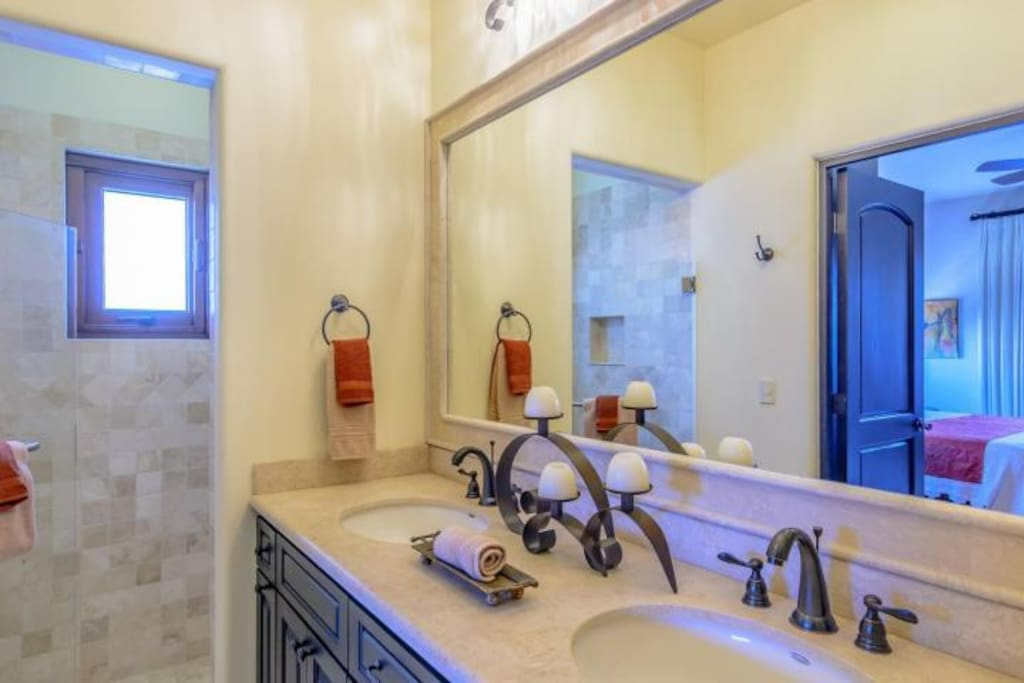 Each bathroom features Travertine counters, shower surrounds and double sinks