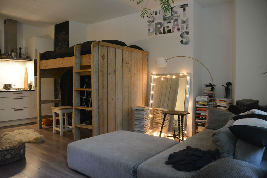 Shared 1 room studio house: the guest's sofa and the wooden loft bed where the hosts sleep