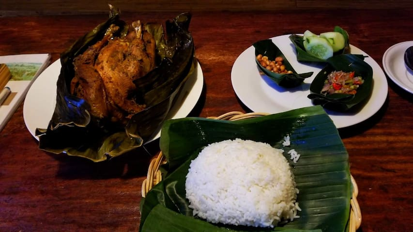 A Balinese Specialty, Ayam Betutu. A whole chicken rubbed in Balinese herbs and spices, wrapped in banana leaves and slow cooked to perfection in its wrapping. A perfect meal for two. Made only to order 36 hours in advance by a lady in a village .