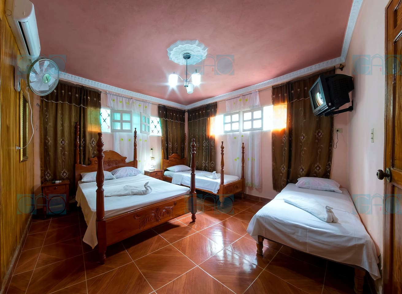 Private bedroom with one double bed, two personal beds, TV, Air conditioning, private bathroom and wetbar  area.