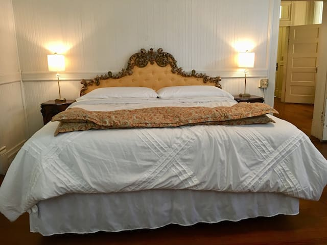"""The antique French headboard is in the master bedroom above a king size bed.  This room was originally the """"Blacks Only"""" waiting room in the depot.  Don't be turned off - learning our true history helps us not to repeat our mistakes!"""