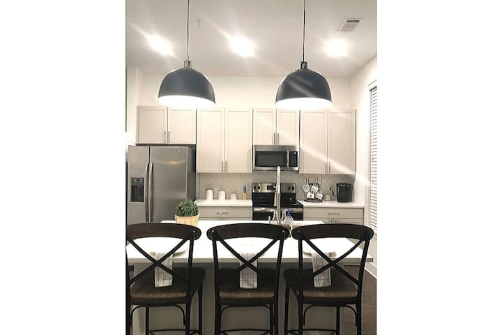 The Kitchen lines a wall and is separated in the open floor plan by an island.   We love hosting and provide amenities such as bottled water, coffee, creamer, basic cooking utensils, and a bright, clean environment.