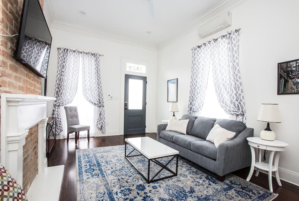 """Living room. Queen sleeper sofa.  55"""" wifi tv.  Looking at front door."""