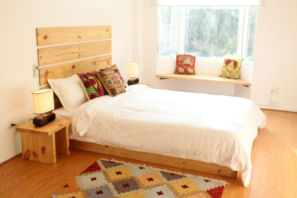 Bedroom with real wood headboard, Tibetan carpet and Bay window seating.