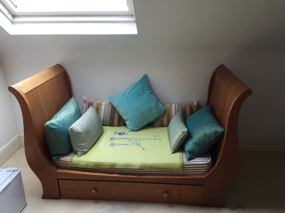 Child's day bed doubling as seat for TV area under large dormer loft window which floods the room with natural light.