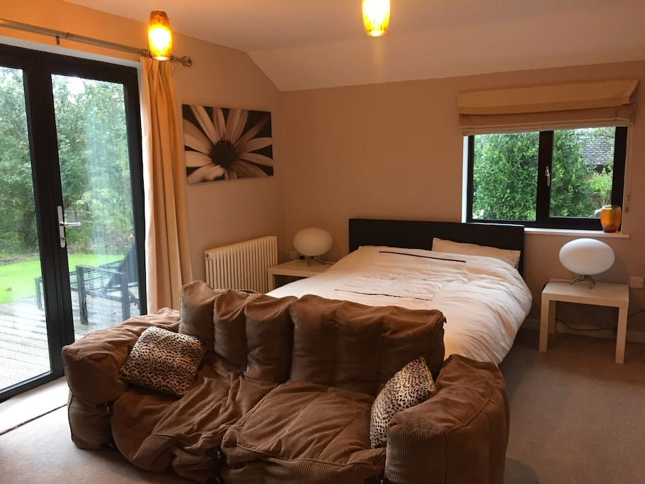 Main room with kingsize bed and beanbag sofa, patio doors lead onto decking and garden