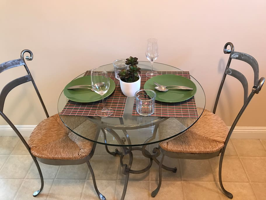Glass table with 2 chairs. Placemats, plates, utensils, wine glasses provided.