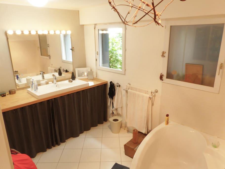 La salle de bain attenante, très claire, avec grande baignoire d'angle et fenêtre sur le jardin.