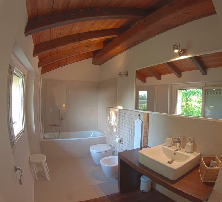 Bagno privato in pietra e legno, con vasca e kit di cortesia
