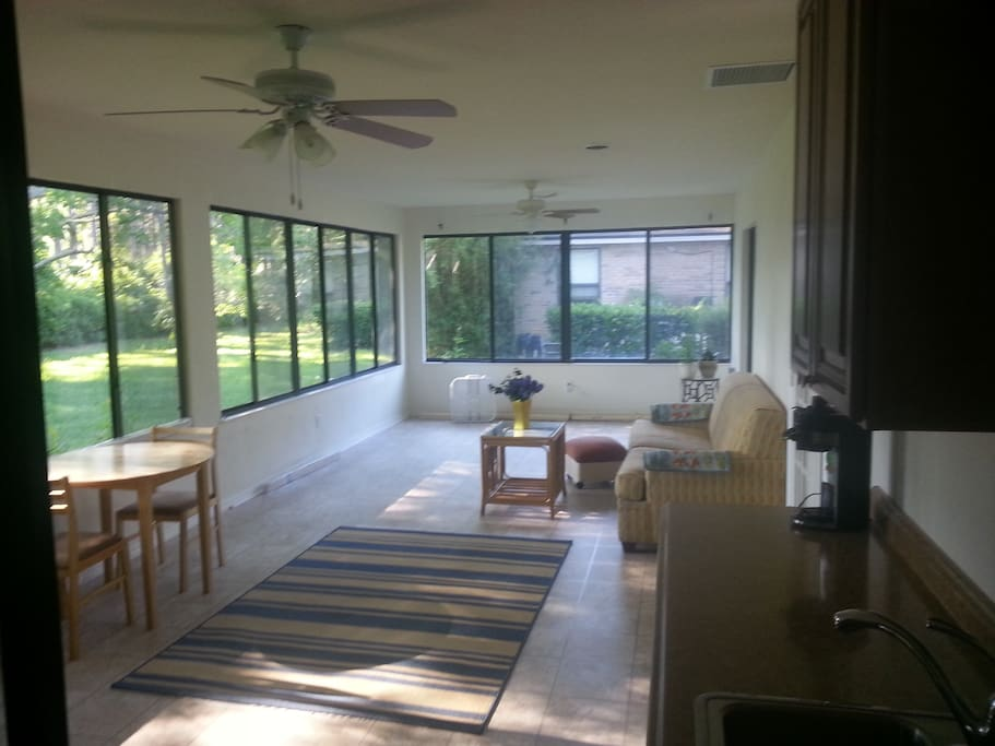 Backyard entrance into sunroom. Small fridge, microwave, nuwave class cooktop burner, coffeemaker in small kitchenette area.
