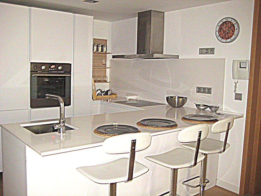Cocina americana totalmente equipada, vitro, lavabajillas, horno, robot de cocina, frigorifico electrolux, vajilla portico, cuberteria mi casa, plancha cocina, vasos, manteles Zara Home, bateria de cocina bra, juego de cuchillos chef