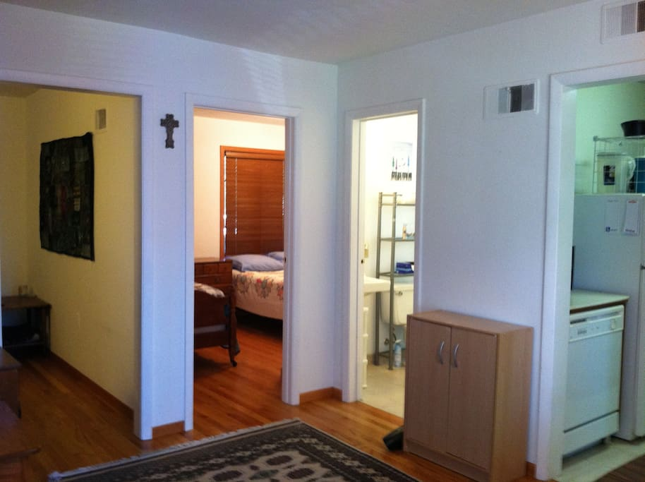 View of inside apartment from entryway; left to right is the TV room (with futon), bedroom, bathroom, and kitchen.