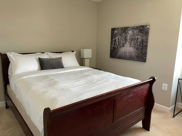 Bedroom 2 features a queen-size bed and personal workstation.