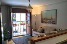Open plan living area with sofa-bed and balcony. Salón-cocina con sofá-cama y balcón.