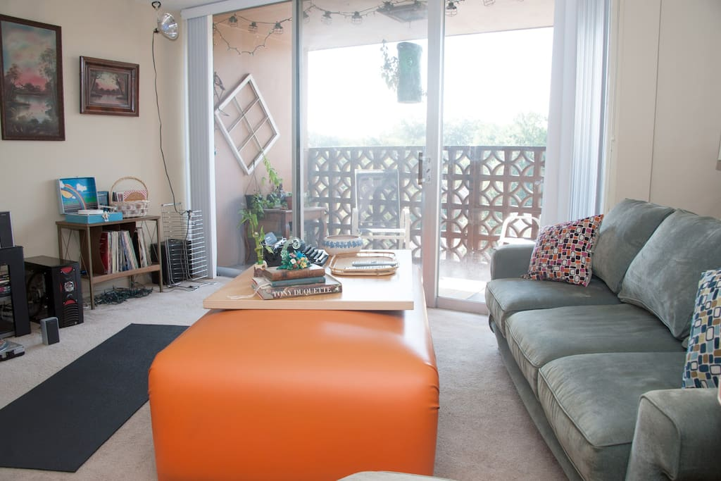 Adjacent to the living room is a balcony that looks over a tree-lined neighborhood.