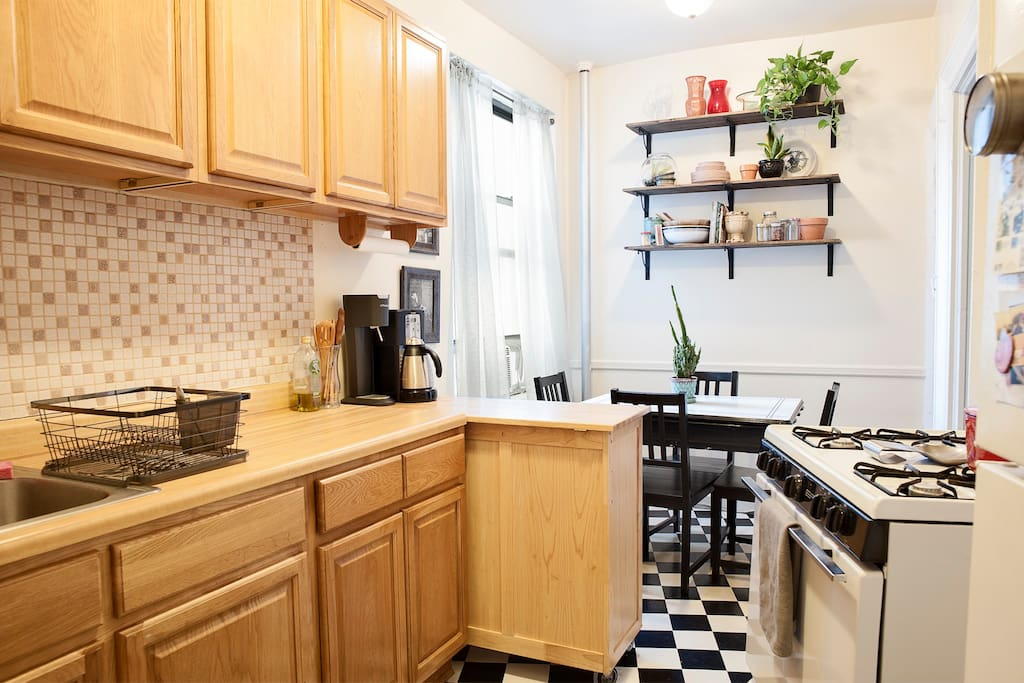 Large kitchen flooded with light, and equipped with a stove, coffee pot, blender, a full-size fridge, and tons of cooking tools. With a table that opens to fit 4-6 people and tons of counter space, it's a great place to make and share a gourmet meal!