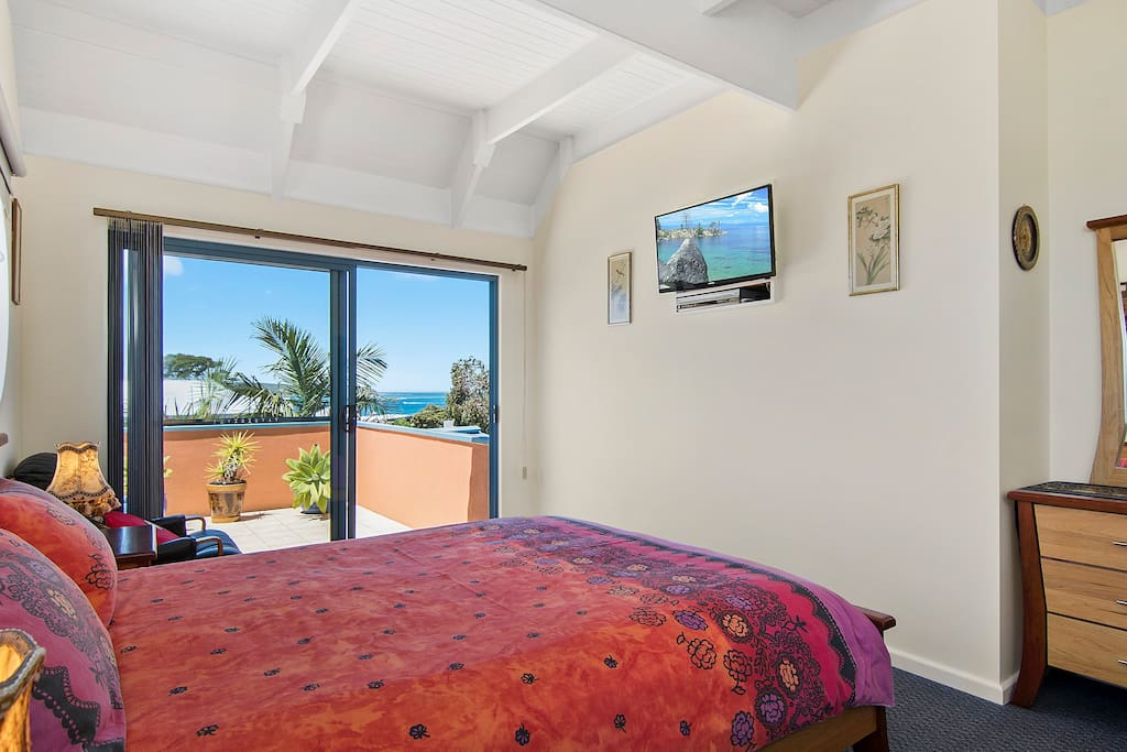 Relax in main bedroom with ocean views. TV & DVD
