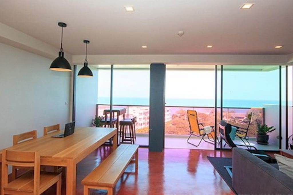 Spacious dinning & living areas with polished concrete floor and bay windows sea view