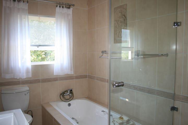 Full bathroom with shower and bath tub.