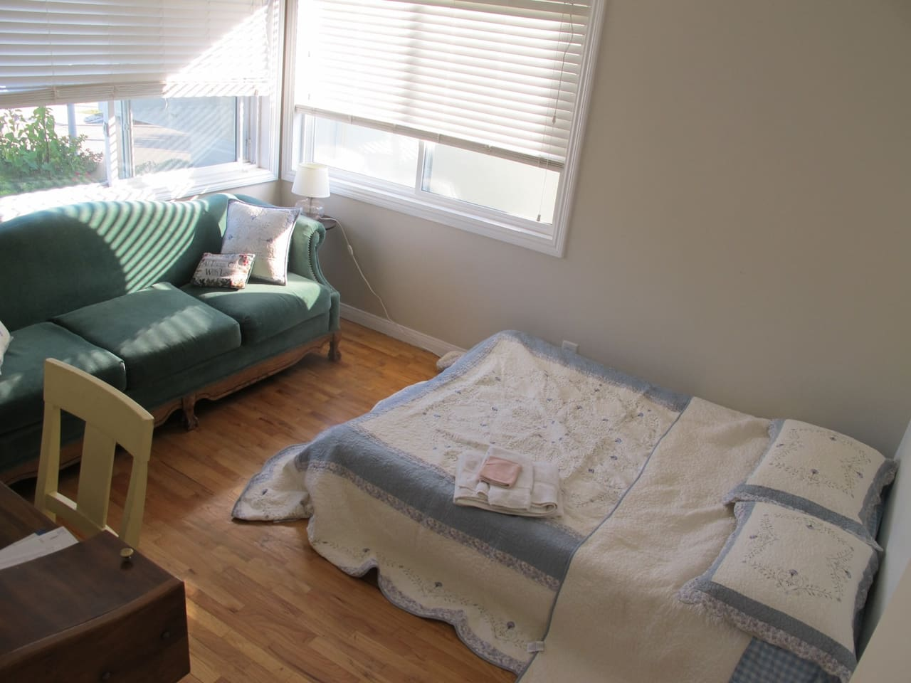 Guest bedroom with couch, desk, and queen sized mattress.