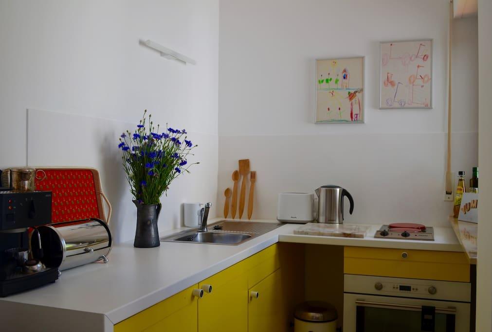 Küche mit Herd, Backofen, Toster, Wasserkocher, Kaffeemaschine und geräumigen Kühlschrank.