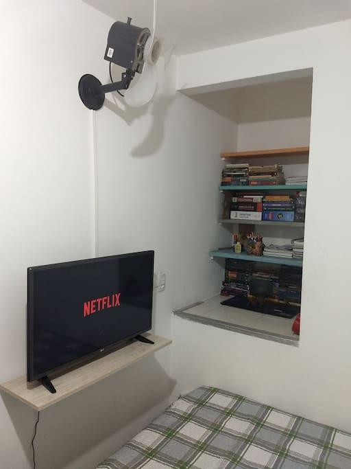 """Vista da TV Smart de 32"""" com Netflix liberada, livros de decoração e ventilador turbo de parede com controle no interruptor."""
