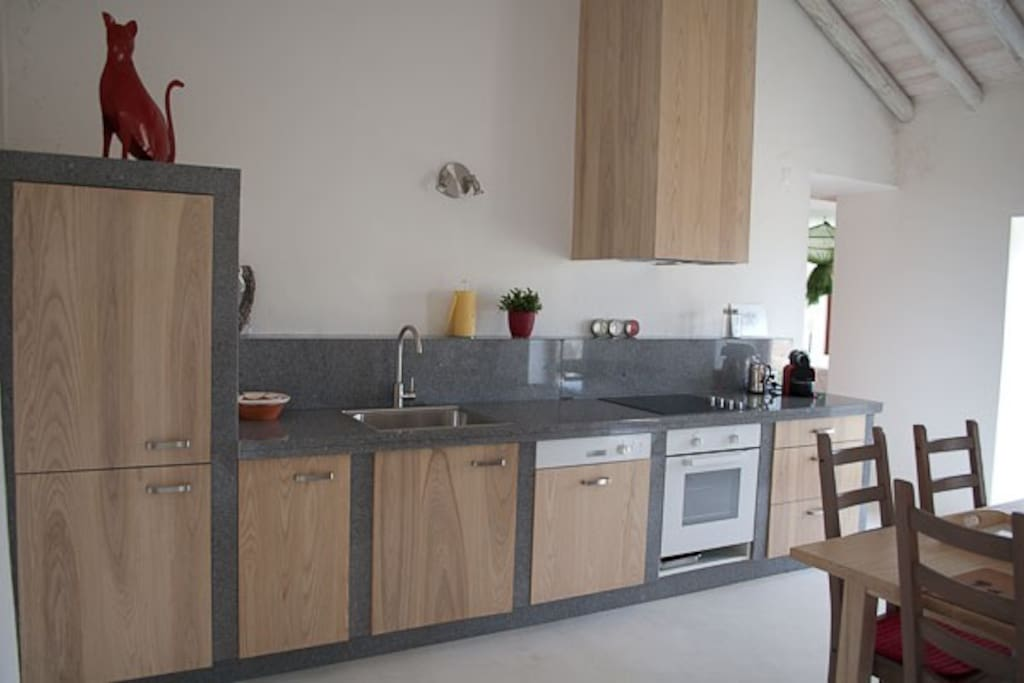 A complete wooden/granite kitchen.